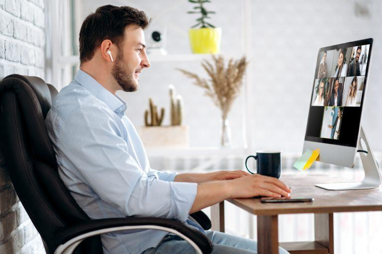 Man working on laptop with online meeting