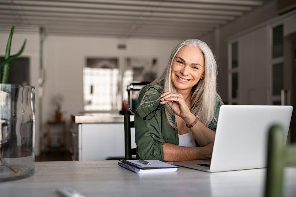 Older woman on laptop in green shirt